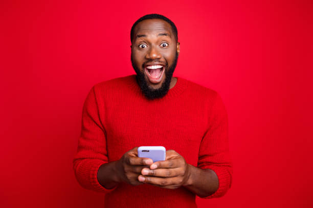 Close-up portrait of his he nice attractive cheerful cheery excited glad bearded guy using wireless connection wi-fi app 5g blog post smm fast speed isolated over bright vivid shine red background stock photo