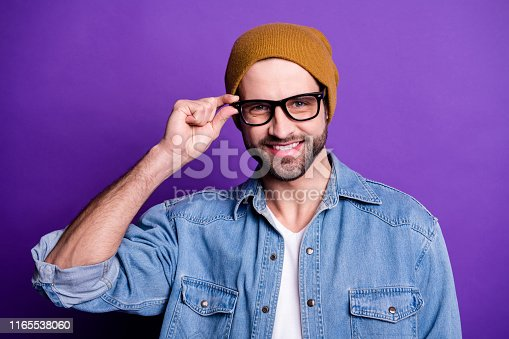 1165538246 istock photo Close-up portrait of his he nice attractive content cool cheerful cheery positive bearded guy touching specs laser sight correction isolated over bright vivid shine violet lilac purple background 1165538060