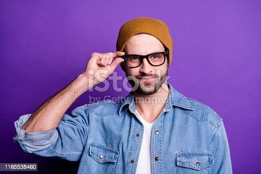 1165538246 istock photo Close-up portrait of his he nice attractive content cool modern cheerful bearded guy touching specs isolated over bright vivid shine violet lilac purple background 1165538460
