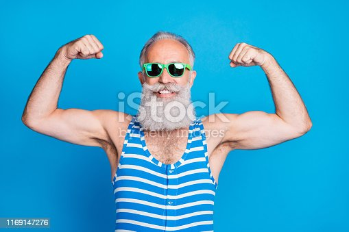 Close-up portrait of his he nice attractive content proud sportive cheerful cheery gray-haired man trainer instructor showing biceps isolated on bright vivid shine turquoise blue green background