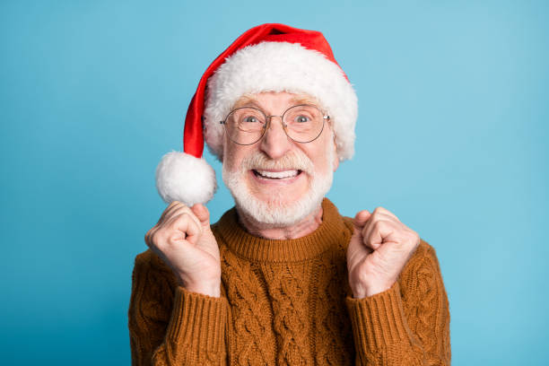 Close-up portrait of his he nice attractive crazy cheerful cheery lucky bearded grey-haired Santa father celebrating great success sale discount December isolated over blue pastel color background stock photo