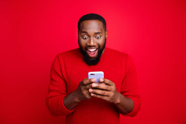 Close-up portrait of his he nice attractive focused cheerful cheery glad excited bearded guy using wireless connection app 5g blog post smm like isolated over bright vivid shine red background stock photo