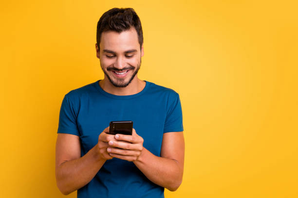 Close-up portrait of his he nice attractive focused cheerful cheery guy using device browsing web internet online wi-fi 5g isolated over bright vivid shine vibrant yellow color background stock photo