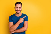istock Close-up portrait of his he nice attractive glad cheerful cheery guy pointing forefinger aside recommend presentation isolated over bright vivid shine vibrant yellow color background 1256127007