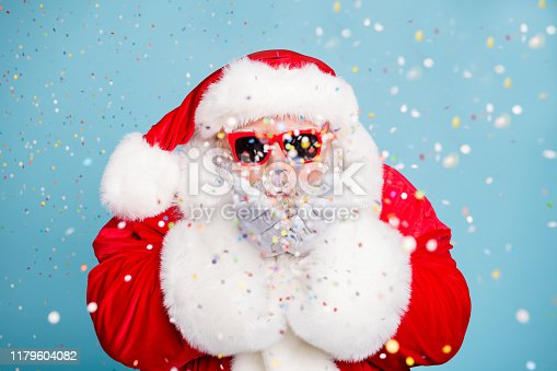 1016084100istockphoto Close-up portrait of his he nice fat dreamy bearded Santa St Saint Nicholas blowing decorative confetti eve noel night fairy isolated over blue turquoise pastel color background 1179604082