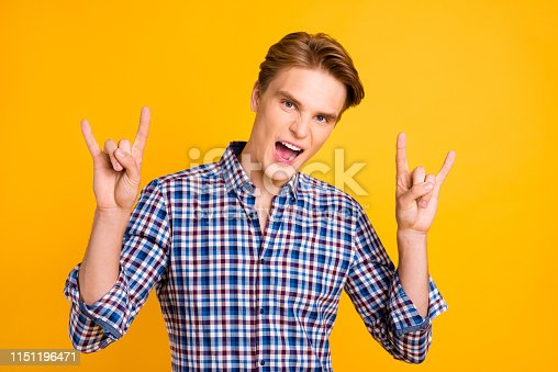 1165538246 istock photo Close-up portrait of his he nice-looking attractive cool cheerful cheery guy wearing checked shirt showing horn symbol heavy metal isolated over bright vivid shine yellow background 1151196471