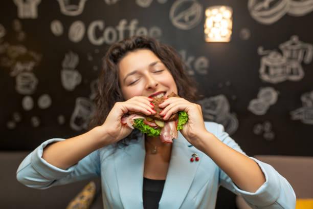 retrato do close up da mulher caucasiano nova com fome, sanduíche da mordida - junk food - fotografias e filmes do acervo