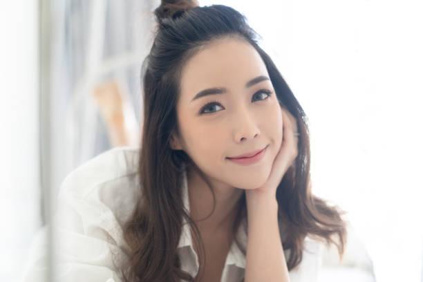 白いベッドのてるのに横たわって、自宅でカメラを見て触発された白人アジアの女性のクローズアップの肖像。コンセプトの女性ライフスタイル。 - 韓国文化 ストックフォトと画像