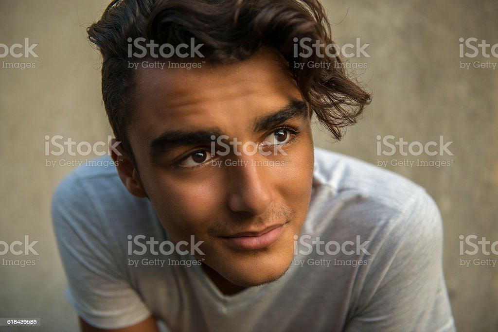 Close-up portrait of leaning young man looking away stock photo