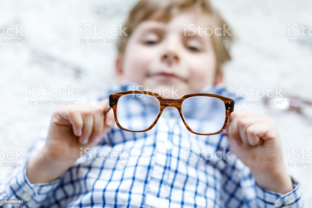 Close-up portrait of little blond kid boy with brown eyeglasses stock photo