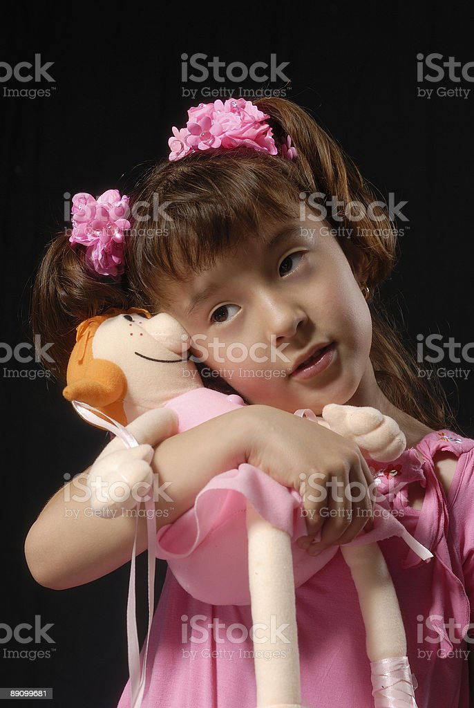 Close-up portrait of a little girl in pink abrazándose tela de muñeca foto de stock libre de derechos