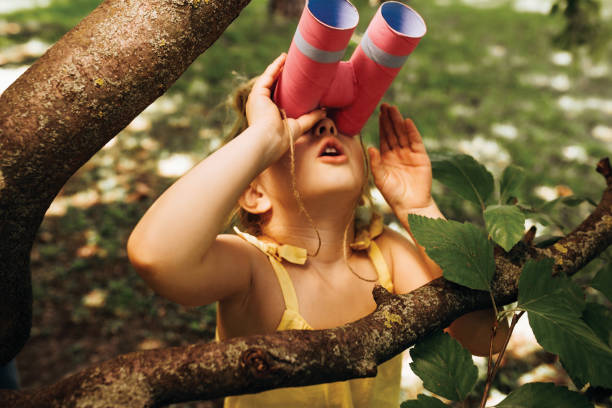 Closeup portrait of little girl looking through a binoculars searching for an imagination or exploration in summer day in park. Child playing with binocular pretend safari game outdoors in the forest stock photo