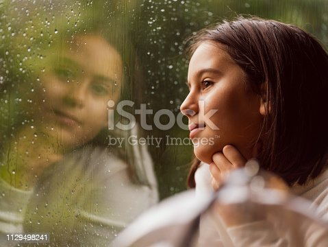 Close-up Portrait of Little Girl Next to Rainy Window