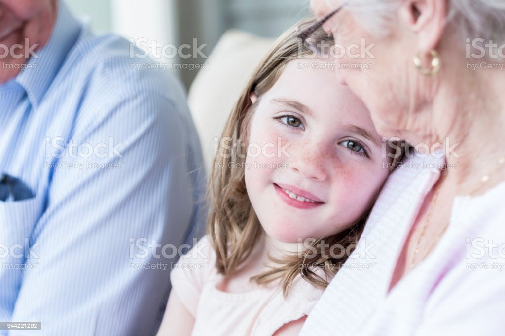 Closeup portrait of little girl sitting with grandparents stock photo