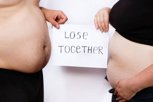 Close-up portrait of man and woman obese bellies and hands holdi stock photo