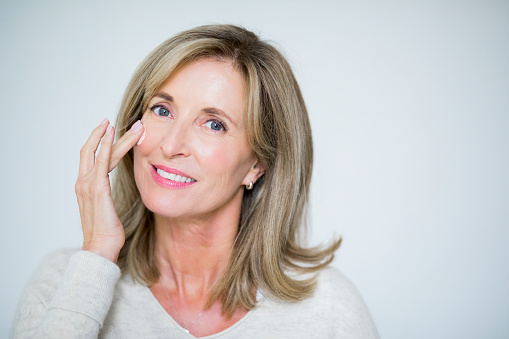 Portrait of mature woman applying moisturizing cream. Beautiful female is taking care of her skin. She is with blond hair against white background.