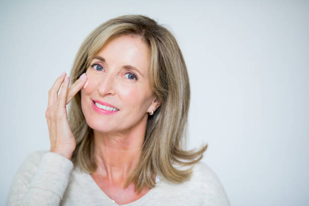 Close-up portrait of mature woman smiling Portrait of mature woman applying moisturizing cream. Beautiful female is taking care of her skin. She is with blond hair against white background. medium length hair stock pictures, royalty-free photos & images