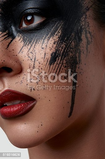 istock Closeup Portrait of Model with black Paint on her Face 519316626