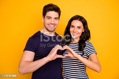 950598260 istock photo Close-up portrait of nice attractive gentle tender sweet cheerful cheery careful married spouses embracing showing heart form shape idyllic harmony isolated on bright vivid shine yellow background 1176787968