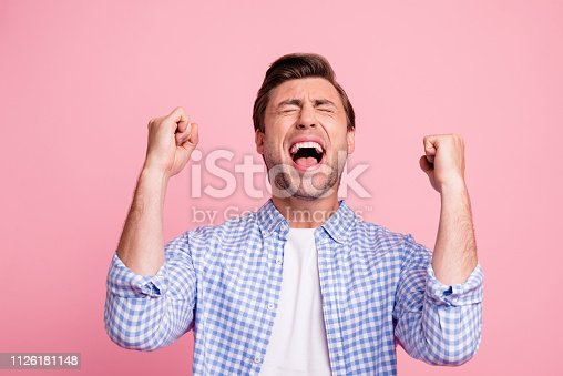 istock Close-up portrait of nice attractive handsome cheerful cheery guy wearing checked shirt best luck holding fists enjoying party isolated over pink pastel background 1126181148