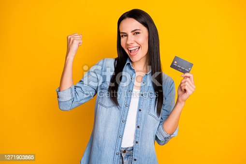 istock Close-up portrait of nice attractive lovely pretty cute cheerful cheery girl holding in hand cell plastic card new solution novelty advert isolated bright vivid shine vibrant yellow color background 1271903865