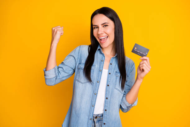 Close-up portrait of nice attractive lovely pretty cute cheerful cheery girl holding in hand cell plastic card new solution novelty advert isolated bright vivid shine vibrant yellow color background stock photo