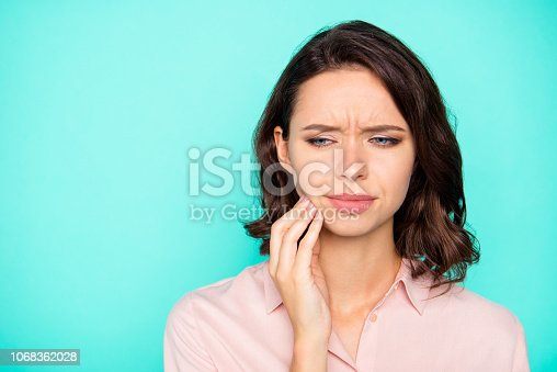 Close-up portrait of nice attractive sad unhealthy lady touching cheek copy empty blank space isolated over turquoise teal pastel background