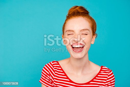 Close-up portrait of nice cute adorable attractive lovely dreamy cheerful glad red-haired girl with bun, wearing tshirt, opened mouth, closed eyes, isolated on teal pastel bright vivid blue background