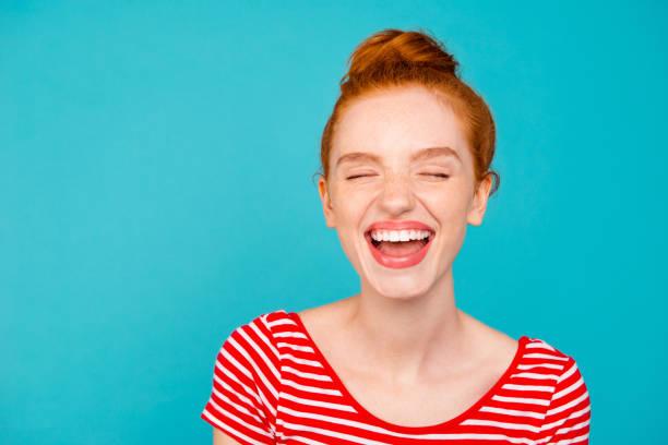 特寫肖像的尼斯逗人喜愛可愛的可愛的夢幻般愉快的紅頭髮的女孩與包子, 穿著 t恤, 張開的嘴, 閉著眼睛, 查出的青色柔和明亮生動的藍色背景 - 露齒的笑容 個照片及圖片檔