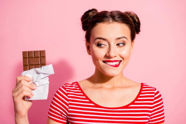 漂亮可愛迷人迷人的迷人的迷人的迷人的開朗的女孩穿著條紋 t恤手看最喜歡的甜點生活方式廣告在粉紅色的背景隔離 - 即食口糧 個照片及圖片檔