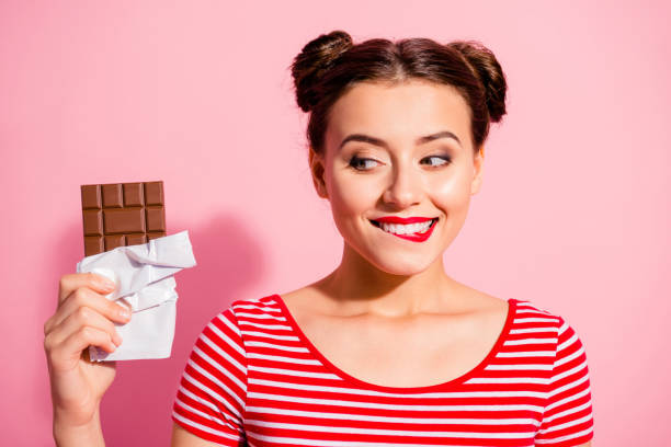 Close-up portrait of nice cute charming attractive winsome glamorous cheerful girl wearing striped t-shirt holding in hands looking favorite dessert life lifestyle advert isolated on pink background Close-up portrait of nice cute charming attractive winsome glamorous cheerful girl wearing striped t-shirt holding in hands looking favorite dessert life lifestyle advert isolated on pink background. temptation stock pictures, royalty-free photos & images