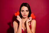 istock Close-up portrait of nice cute sweet tender adorable winsome attractive lovely gorgeous lady girlfriend holding in hands two small hearts isolated over burgundy maroon background 1127552832