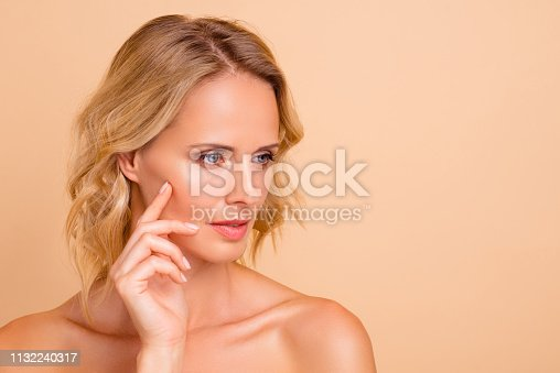 istock Close-up portrait of nice dreamy attractive adorable wavy-haired lady with flawless shine fresh skin touching cheek lifting botox collagen copy empty blank space isolated on beige background 1132240317