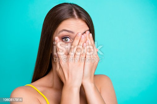 istock Close-up portrait of nice funny shocked attractive straight-haired girl, covering face with palms, one eye peeping, isolated on green turquoise background 1060817914