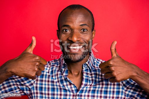 Close-up portrait of nice handsome cheerful cheery positive optimistic guy wearing checked shirt showing double thumbup isolated over bright vivid red background