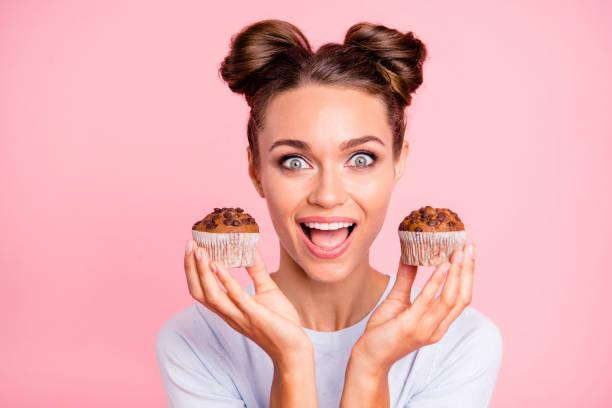 primer plano retrato de hermoso exquisita atractivo divertida alegre positivo loco chica sosteniendo en las manos dos tortas hambriento abrió boca aislado sobre fondo rosa pastel - magdalena dulces fotografías e imágenes de stock