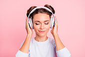 Close-up portrait of nice lovely sweet attractive calm peaceful conecnrated focused girl wearing touching earphones closed eyes isolated over pink pastel background