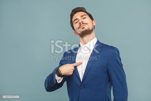 Closeup portrait of proud man pointing finger himself. Business people concept, richly and success. Indoor, studio shot on light blue background