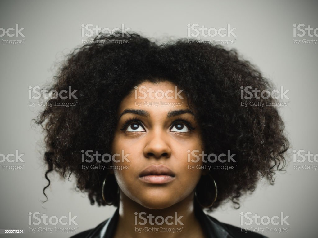 Close-up portrait of real young black woman looking up against gray...