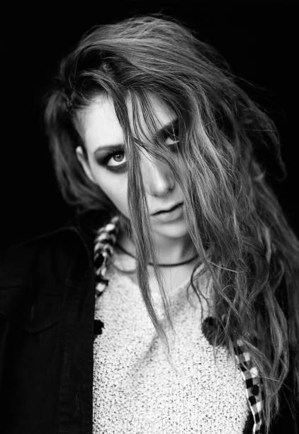 Close-up portrait of sad lovely grunge (rock) girl. Black and white stock photo