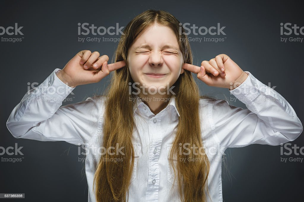 Closeup portrait of screaming girl covering her ears, observing. Hear stock photo