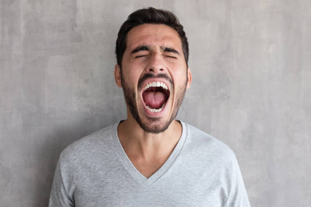 Closeup portrait of screaming with closed eyes crazy young man, standing against gray textured wall Closeup portrait of screaming with closed eyes crazy young man, standing against gray textured wall crying stock pictures, royalty-free photos & images