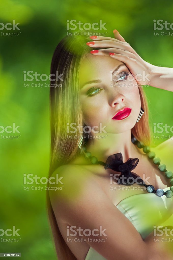 Close-up portrait of sensuality young woman with your hands near the head,long hair, a red lips, a thoughtful gaze at the open air in the middle of green blurred leaves at sunny spring day stock photo
