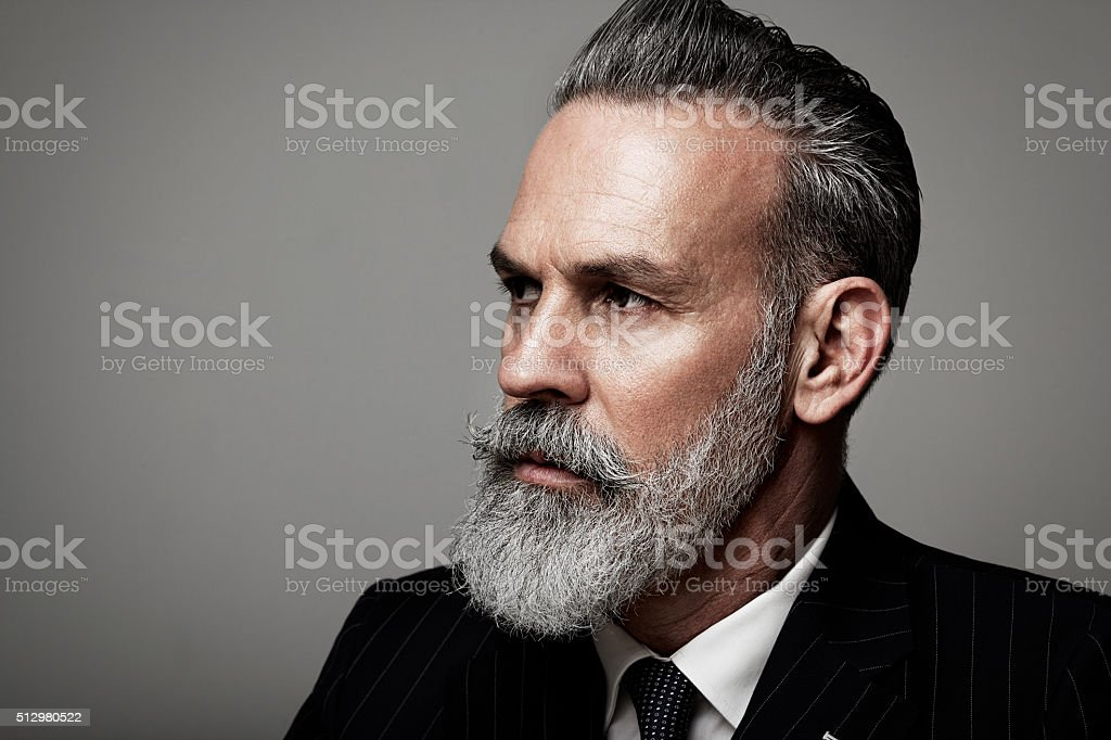 Closeup portrait of serious adult businessman wearing trendy suit  against stock photo