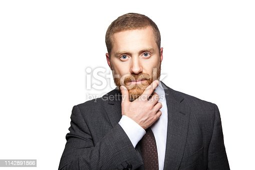 498403166 istock photo Closeup portrait of serious calm handsome businessman with facial beard in black suit standing, relaxed, touching his face and looking at camera. 1142891866