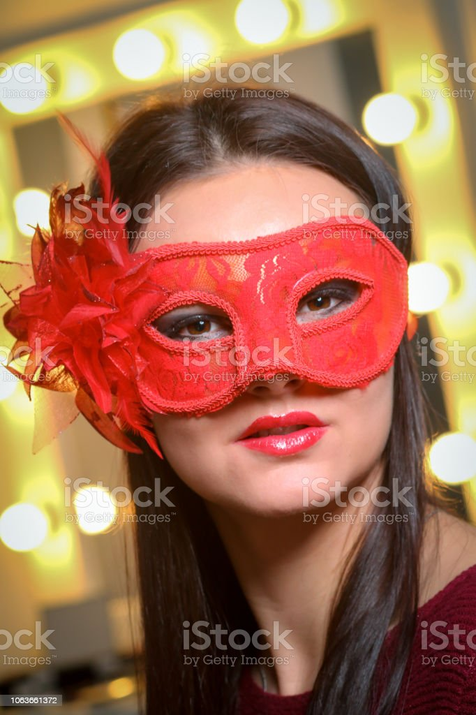 Closeup portrait of sexy woman in red, gold party mask for desire...