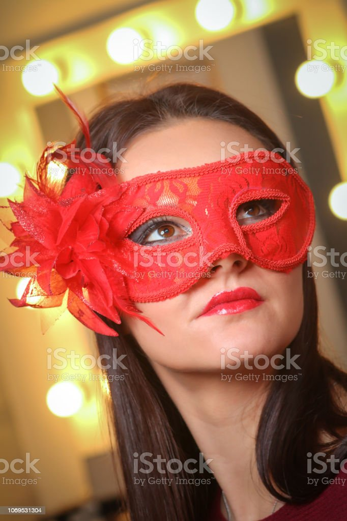 Closeup portrait of sexy woman in red, gold party mask for desire concept at New Year and Christmas party stock photo