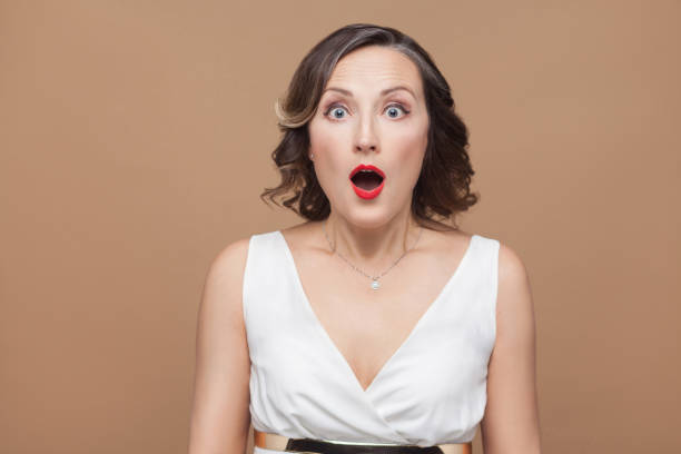 Closeup portrait of shocked adult woman Closeup portrait of shocked adult woman. Emotional expressing woman in white dress, red lips and dark curly hairstyle. Studio shot, indoor, isolated on beige or light brown background one mature woman only stock pictures, royalty-free photos & images
