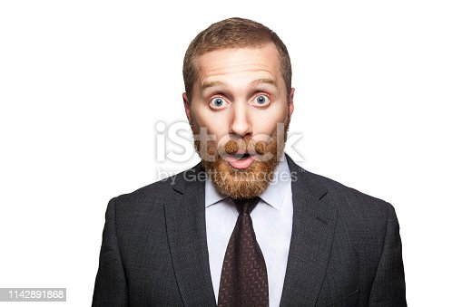 498403166 istock photo Closeup portrait of shocked handsome businessman with facial beard in black suit standing and looking at camera with big eyes and open mouth. 1142891868