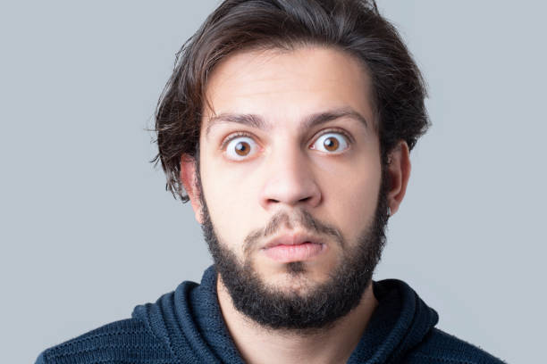 Close-up portrait of shocked young man looking at camera over gray background